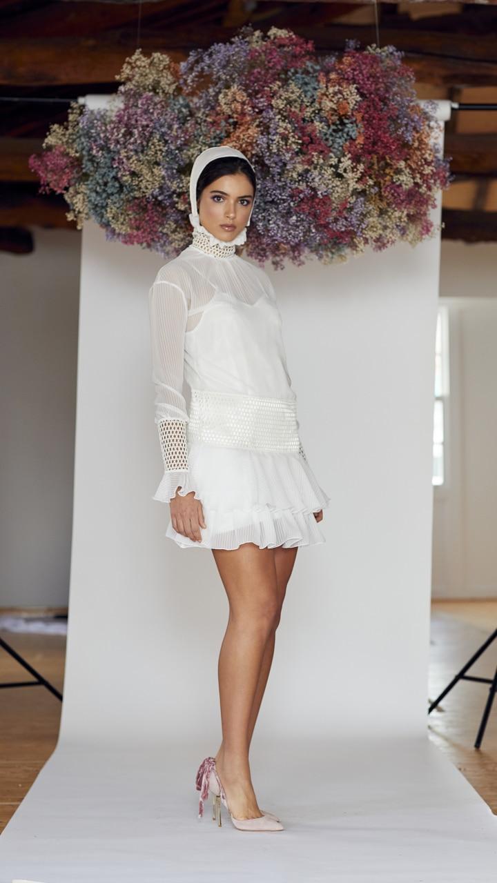 Vestido de novia hecho a medida en atelier de A Coruña. Sobrevestido realizado en gasa efecto plisado degradado, mini, recto con volantes en bajo. Manga abullonada y cannage en cuello alto, cadera y puños.