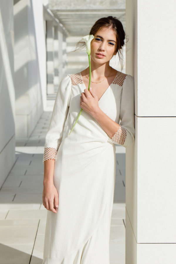 Vestido de novia hecho a medida en atelier de A Coruña. Vestido cruzado con lazada en la espalda. Escote pico, manga francesa y canesúes de guipur de algodón. Bajo con volante asimétrico enseñando los pies. Realizado en seda rústica.