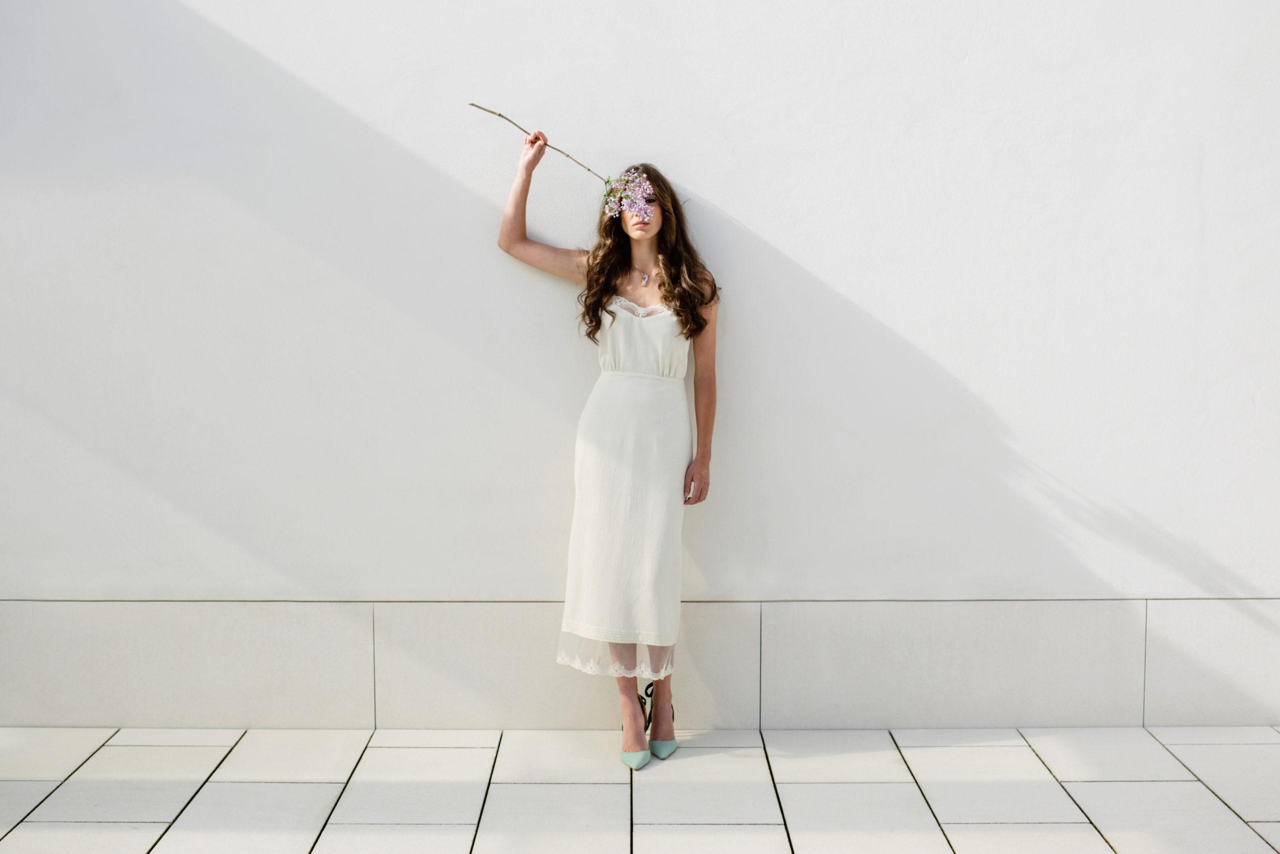 Vestido de novia hecho a medida en atelier de A Coruña. Vestido lencero realizado en seda rústica. Cuerpo con tirantes y puntilla en escote, ablusado en cintura. Falda midi recta con puntilla en bajo.