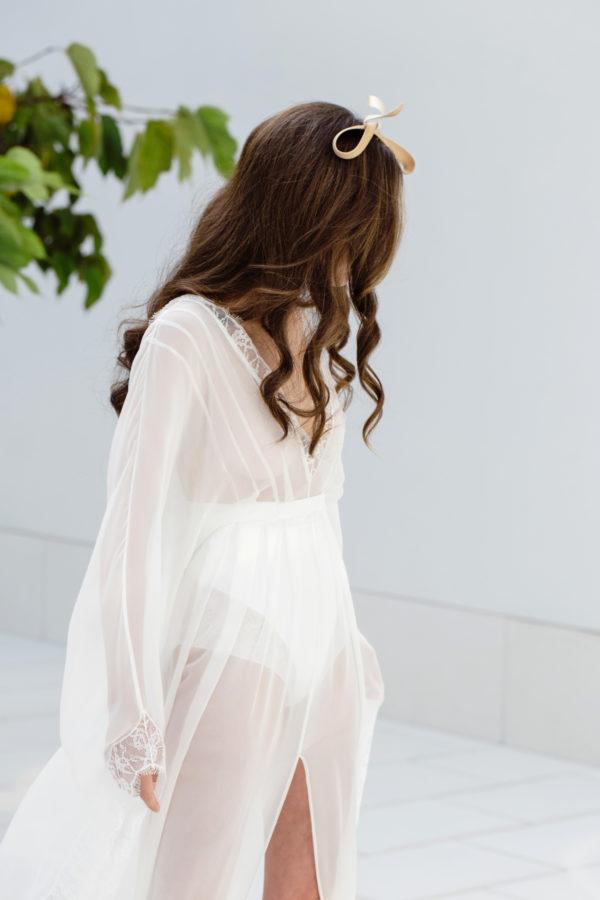 Vestido de novia hecho a medida en atelier de A Coruña. Sobrevestido transparente estilo kimono realizado en gasa de seda. Manga larga, cola, escote pico y abertura central en falda. Puntilla en bajos y escotes.