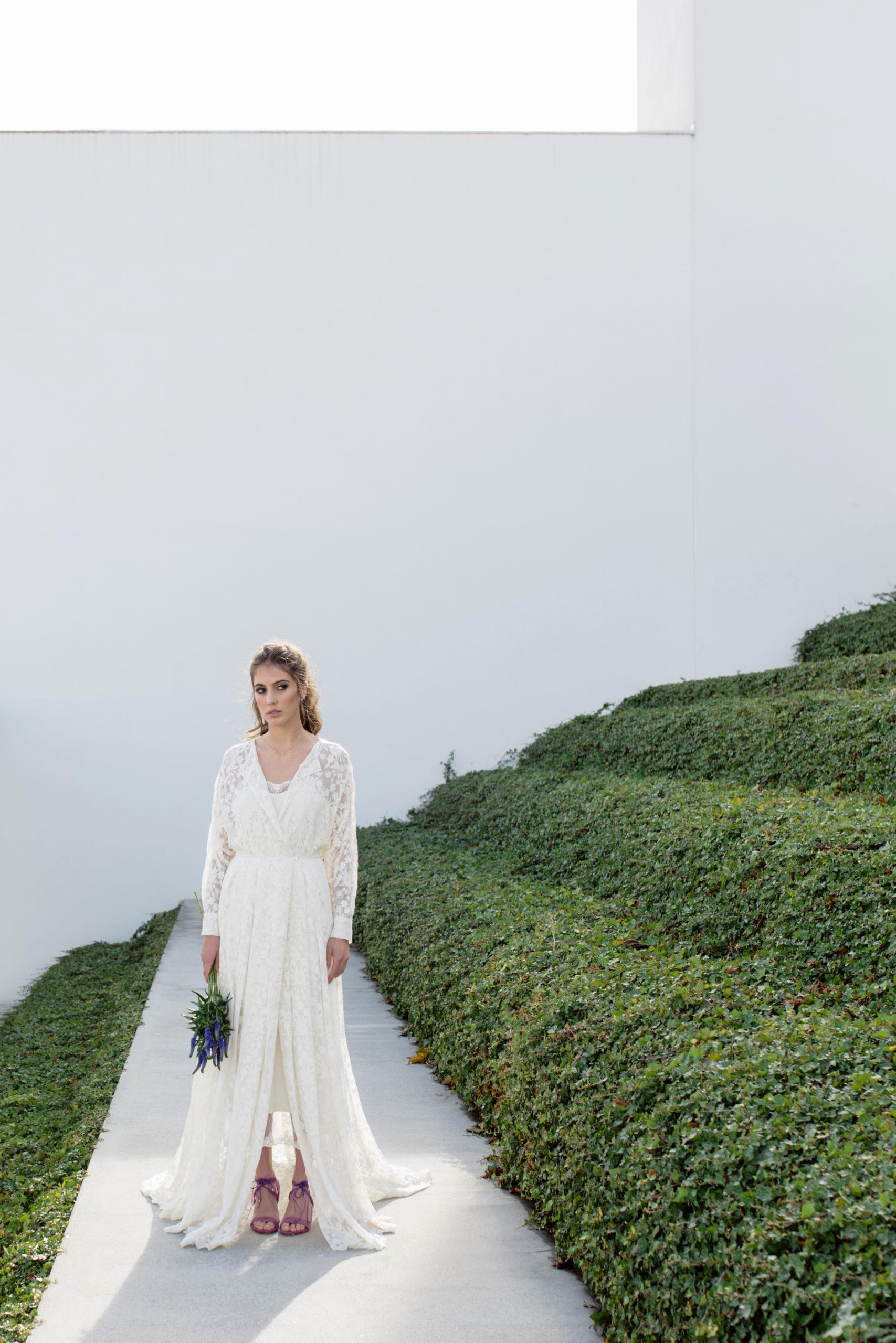 Vestido de novia hecho a medida en atelier de A Coruña. Sobrevestido camisero realizado en gasa de seda bordada. Cuerpo ablusado, manga larga ranglan y falda larga tableada y con cola.
