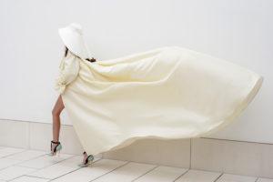 Vestido de novia hecho a medida en atelier de A Coruña. Abrigo de novia inspiración años 60 con tablones en espalda y larga cola. Canesú, escote recto y manga abullonada rematada con una lazada en los puños. Realizado en raso duchesse.